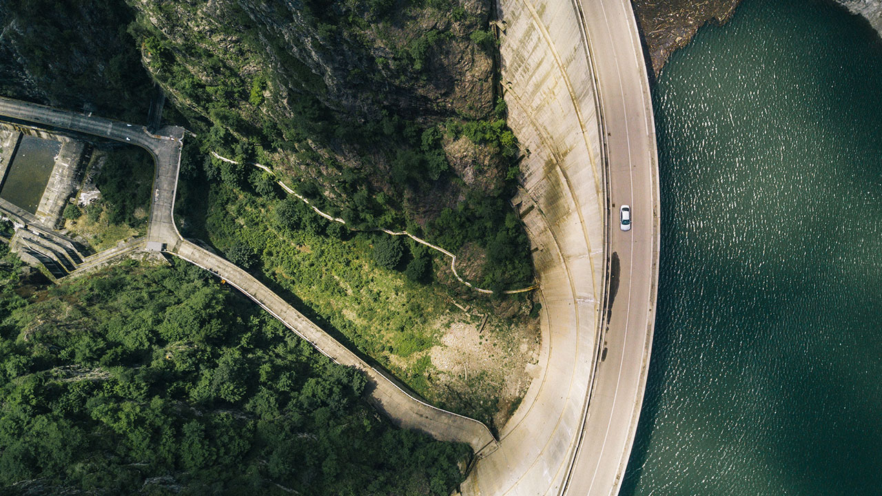 Overhead view of lake and road with a car driving through the mountains